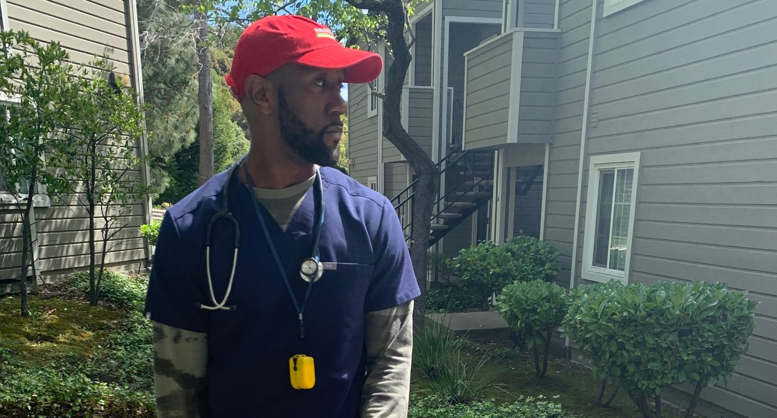 "Michael Flood Jr., a Black home health therapist, stands on an apartment building pathway looking to the side. He is wearing dark blue scrubs, a stethoscope, and a red baseball cap that reads ""Essential Healthcare Staffing"""